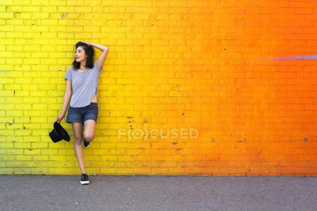 Jeune femme appuyée contre un mur de briques jaunes — Photo de stock