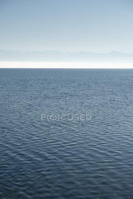 Visão diurna da superfície da água do lago com montanhas no fundo — Fotografia de Stock
