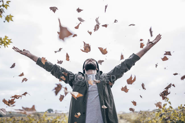 Man throwing autumn leaves in air — Stock Photo
