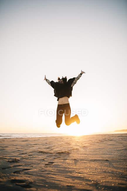 Donna che salta in aria sulla spiaggia — Foto stock