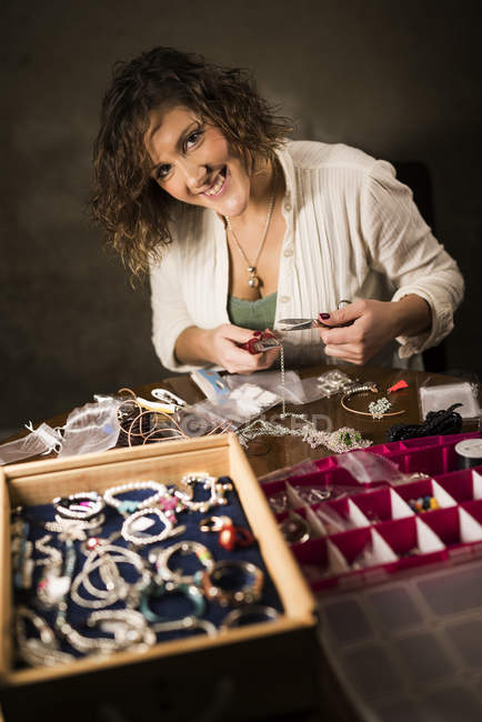 Young woman tailoring with jewelry — Stock Photo