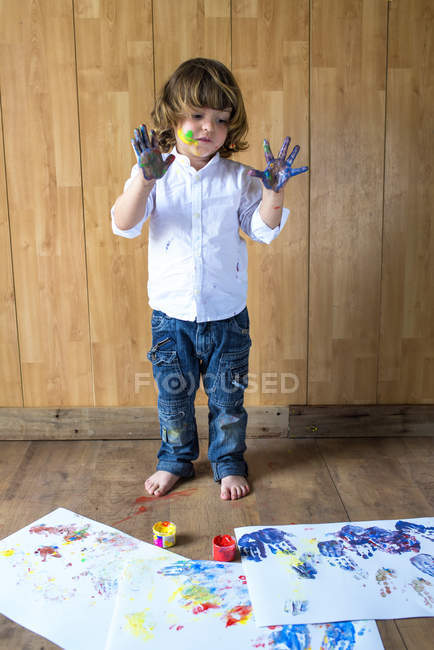 Portrait of creative little boy with palms full of finger colours — Stock Photo