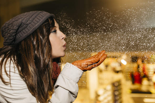 Young woman blowing snow in the air at night — Stock Photo