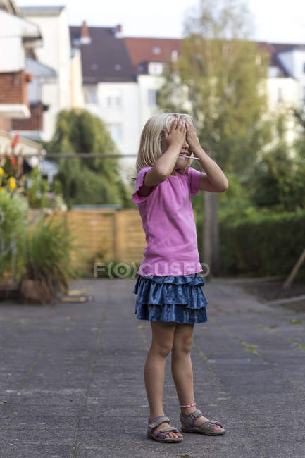 Menina a brincar de esconde e procurar — Fotografia de Stock