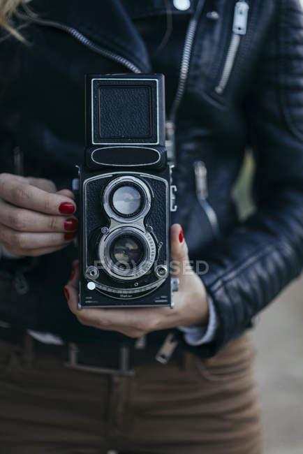 Woman using vintage camera, close-up — Stock Photo