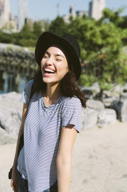 USA, New York City, portrait of laughing young woman wearing black hat — Stock Photo