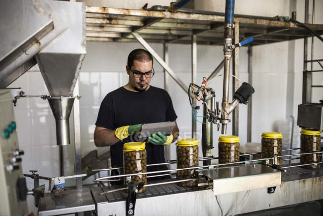 Man in factory using digital tablet at conveyor belt with filled olive glasses — Stock Photo