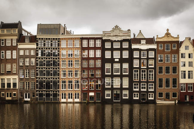 Netherlands, Amsterdam, Row of houses and boat on water — Stock Photo