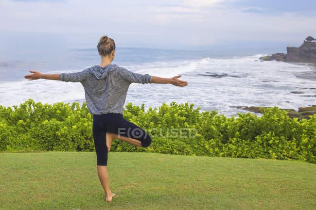 Индонезия, Бали, Танах Лот, женщина, практикующая йогу на побережье — стоковое фото