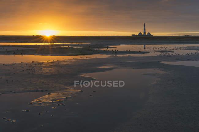 Tideland côte de la mer du Nord, vue du phare de Westerheversand, Allemagne, Schleswig-Holstein, au lever du soleil — Photo de stock
