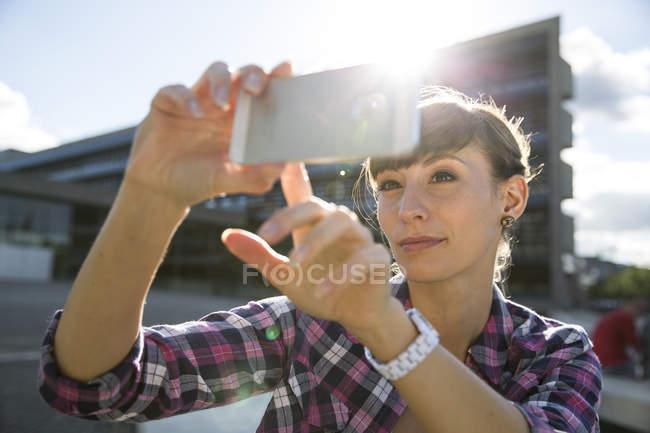 Porträt der jungen Frau, die eine Selfie mit smartphone — Stockfoto