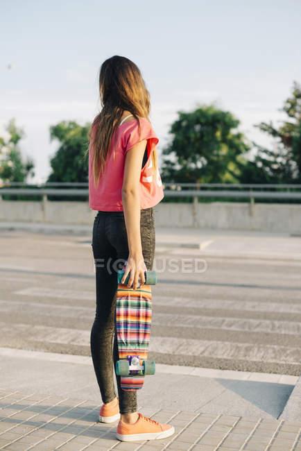 Вид сзади с Скейтборд девушка — стоковое фото