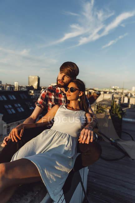 Молода пара, насолоджуючись романтичний захід сонця на терасі на даху — стокове фото