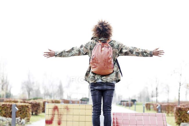 Vista traseira do homem com mochila e braços esticados — Fotografia de Stock