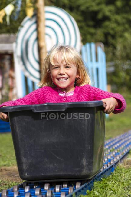 Menina loira sentado em caixa de sabão — Fotografia de Stock