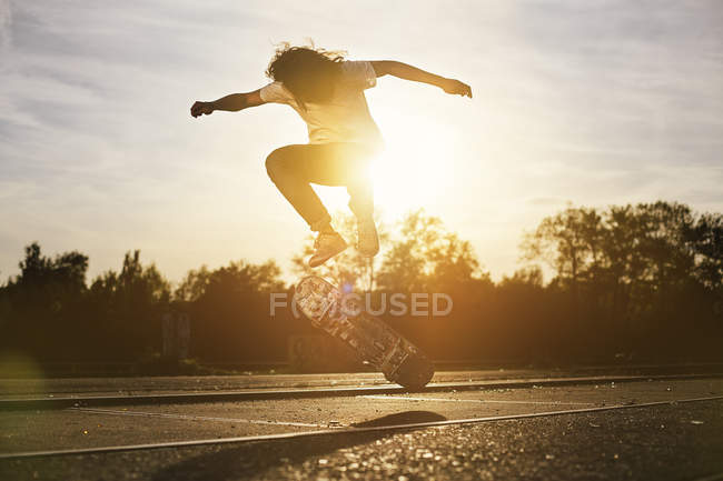 Young man on skateboard in backlight — Stock Photo