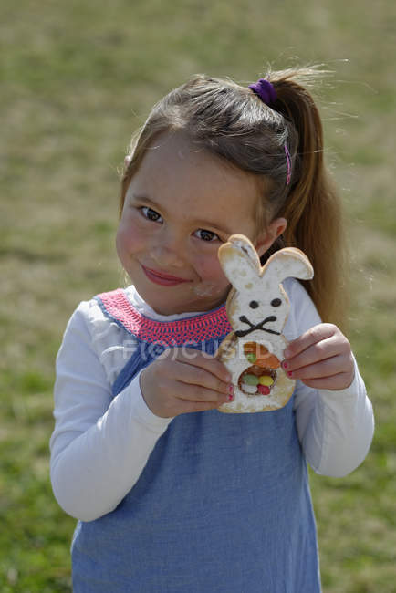 Portrait of smiling little girl showing pastry formed like an Eastern Bunny — Stock Photo