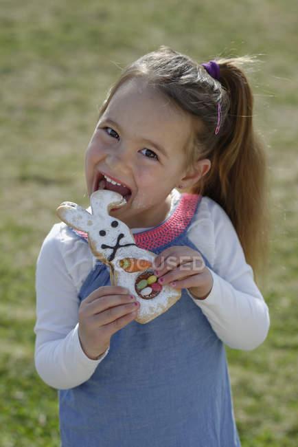 Portrait de fillette souriante arrachant pâtisserie formé comme un lapin oriental — Photo de stock