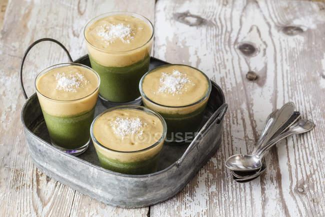 Зеленые коктейли, десерт с ванильным соусом, сырая еда — стоковое фото
