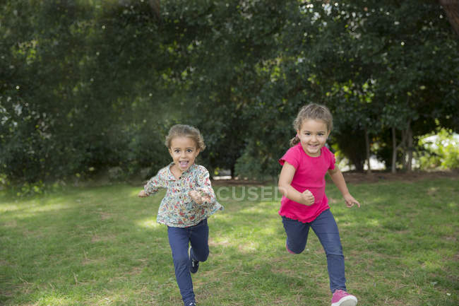 Two smiling girls running in a park — Stock Photo