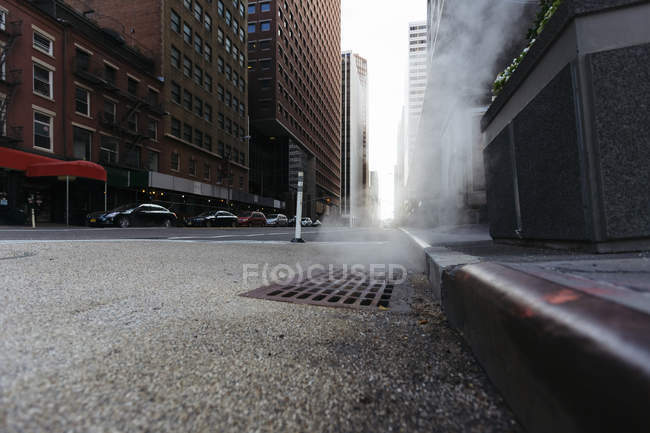 USA, New York City, Downtown Manhattan, haze coming out of a gully in the morning — Stock Photo