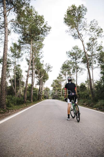 Велосипедист с велосипедом стоит на дороге — стоковое фото
