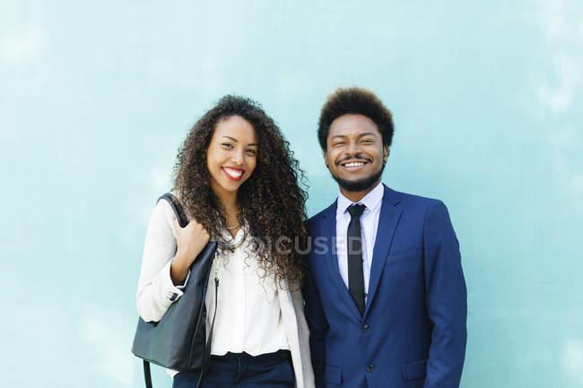 Портрет двух улыбающихся молодых бизнесменов, стоящих перед синей стеной — стоковое фото