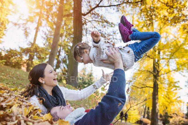 Família feliz se divertindo no parque outonal — Fotografia de Stock