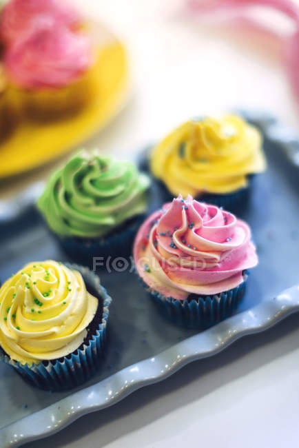 Closeup view of cupcakes with colorful icing on tray — Stock Photo