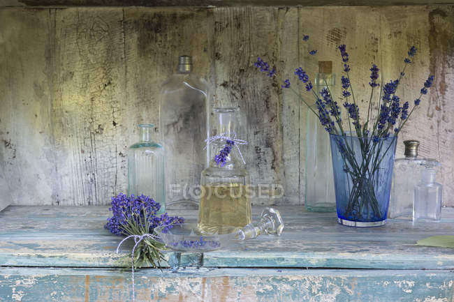 Lavender oil with flowers and glass bottles — Stock Photo