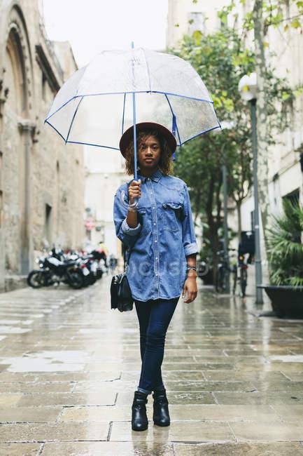 Donna in piedi con ombrello sulla strada — Foto stock