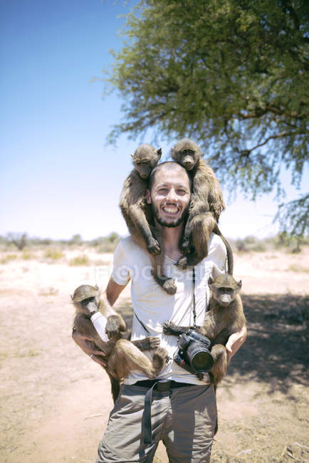 Namibia, man with camera holding four baby baboons — Stock Photo