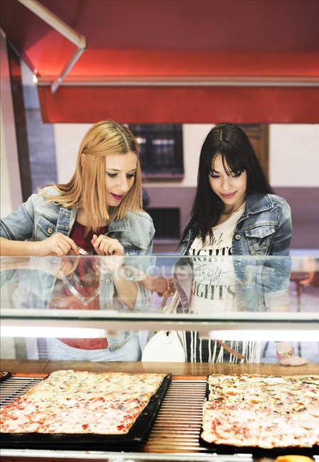 Two young women choosing take away pizza — Stock Photo