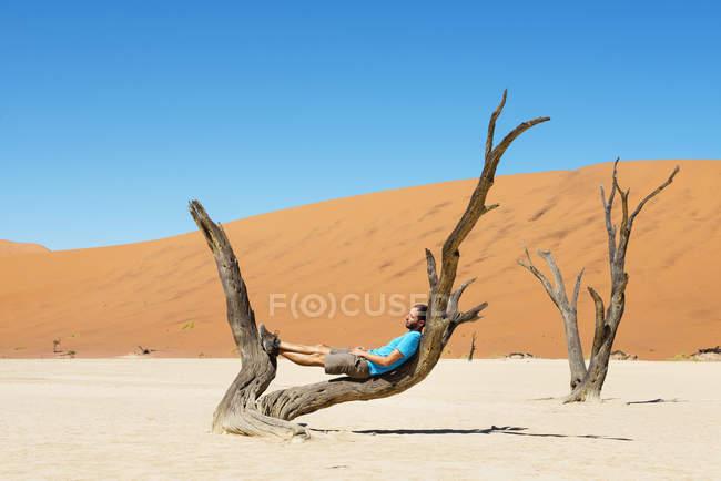 Namibia, Namib-Wüste, Mann ruht auf abgestorbenen Baum im Deadvlei tagsüber — Stockfoto