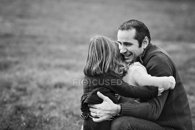 Little girls hugging father outdoors — Stock Photo