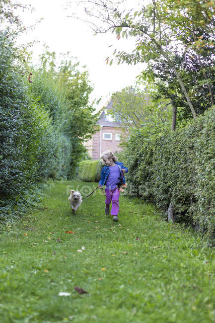 Girl running on meadow with mongrel — Stock Photo