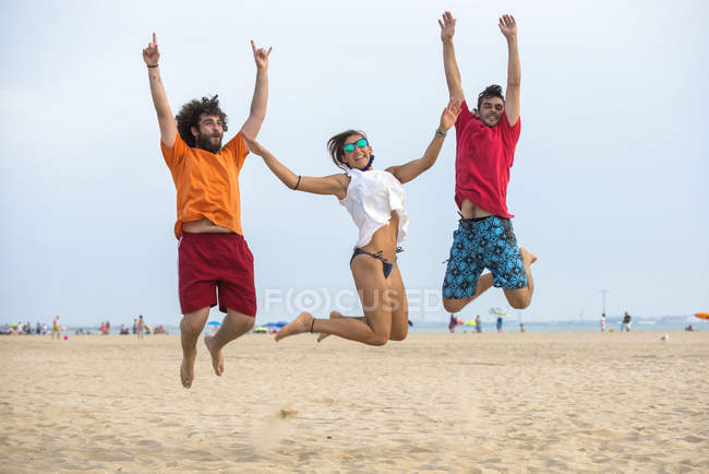 Spain, Cadiz, El Puerto de Santa Maria, Friends jumping on the beach — Stock Photo