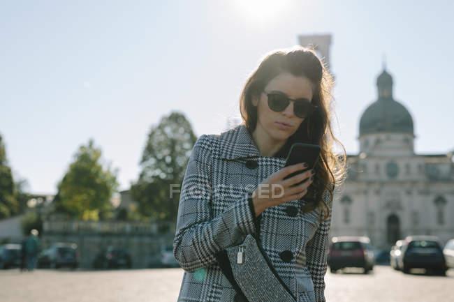 Donna che indossa cappotto a scacchi e occhiali da sole guardando il telefono cellulare — Foto stock