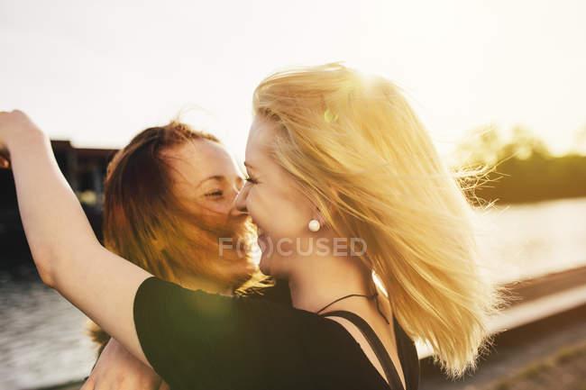 Dois amigos felizes abraçando à beira-mar — Fotografia de Stock