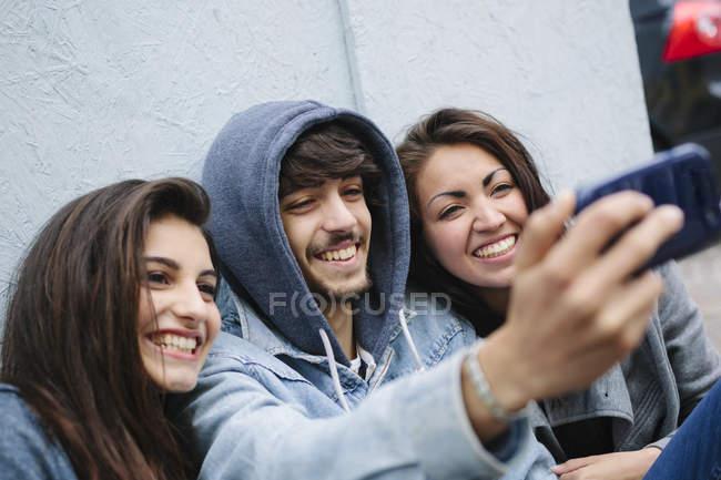 Três amigos tomando uma selfie com telefone celular — Fotografia de Stock