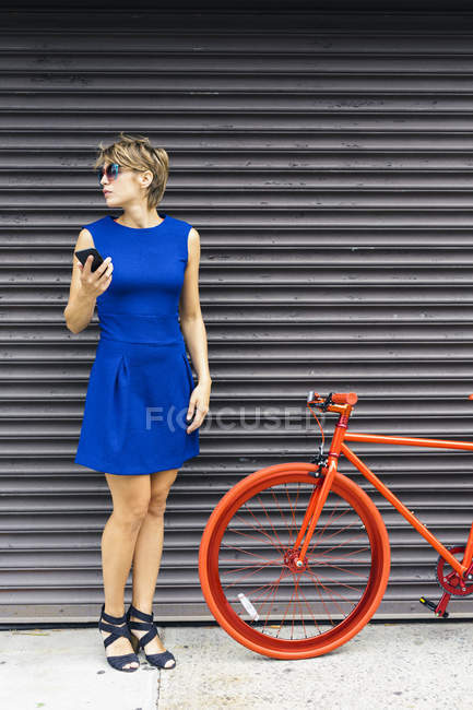 Woman with smartphone and red racing cycle waiting in font of roller shutter — Stock Photo