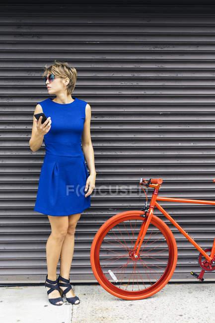 Женщина с смартфонов и Красный гоночный цикла ожидания в шрифте рольставни — стоковое фото