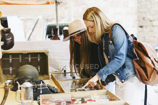 Two young women standing at stall on flea market — Stock Photo