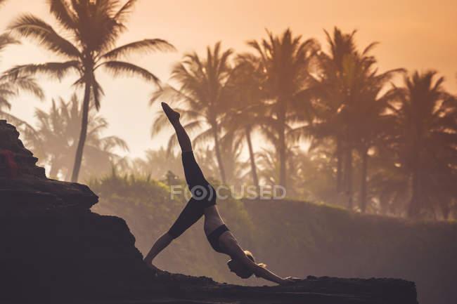 Индонезия, Бали, женщина, практикующая йогу на побережье в сумерках — стоковое фото