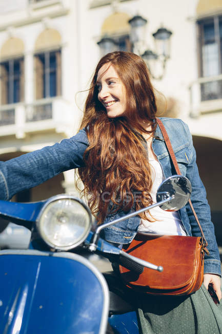 Smiling woman with scooter outdoors — Stock Photo