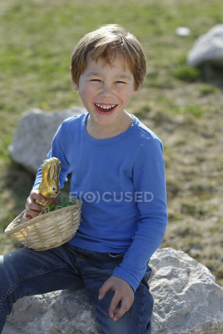 Portrait of laughing little boy with Easter nest and Easter bunny — Stock Photo