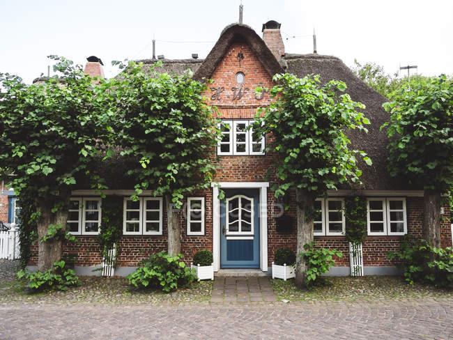 De Alemania, Schleswig-Holstein, isla de Foehr, Nieblum, antiguo capitán la casa con árboles y plantas contra las paredes - foto de stock