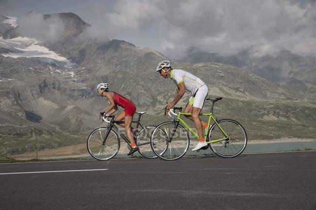 Два велосипедиста на перевале Бернина перед ледником Мортерач — стоковое фото
