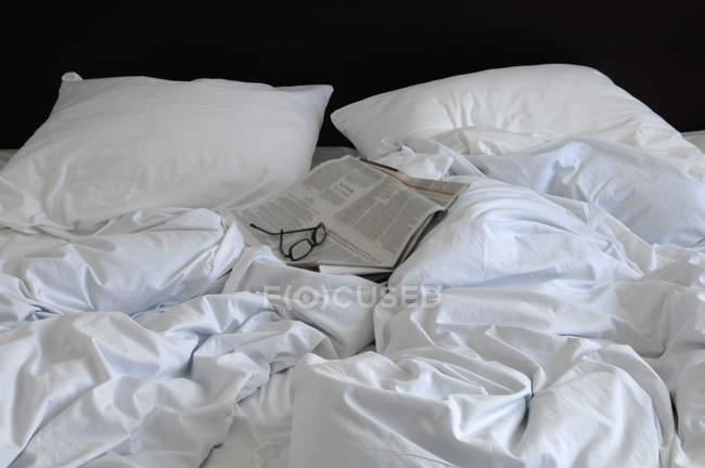 Cama branca enrugada com óculos e jornal — Fotografia de Stock