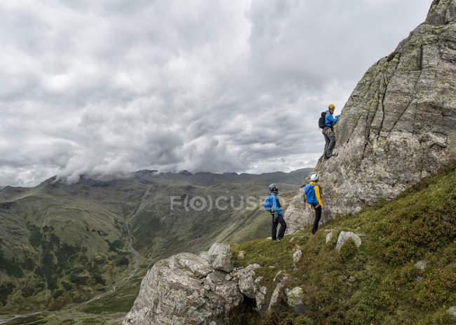 UK, Lake District, Great Langdale, climbers scrambling at Pike of Stickle — Stock Photo